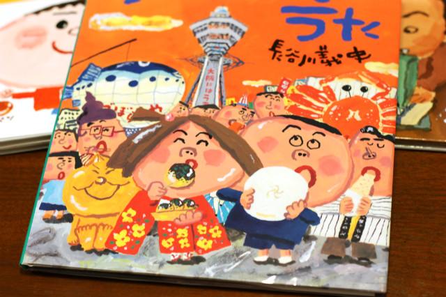 『大阪うまいもんのうた』表紙のたこやきやいかやきを指差す