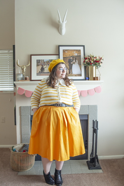 An outfit consisting of a yellow beret, white and yellow striped button down caridgan buttoned as a top and tucked into a yellow pleated midi skirt and black ankle boots.