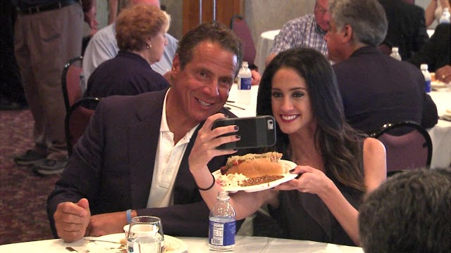 "Late Update :New York Governor Cuomo tells a female correspondent, Beth Cefalu,who filmed the conversation ""I want to see you eat the whole sausage""."