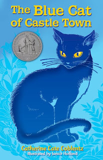Book, 'The Blue Cat of Castle Town' by Catherine Cate Coblentz. Image depicts a dark-blue cat with yellow eyes, against a light-blue background. Gray medallion on cover identifies the book as a Newbery Award Honor Book.