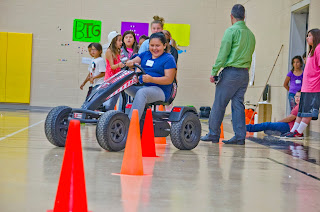 Girl driving cart around cones in gym
