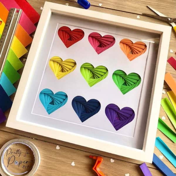 folded hearts in rainbow colors shown in square white frame surrounded by paper crafting supplies