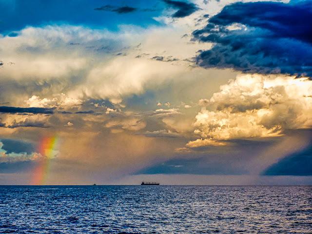 Parte de un arco iris,grandes nubes y un barco en el mar