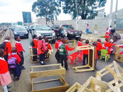 Photos: Primary school pupils in Kenya block road with desks after their school was demolished