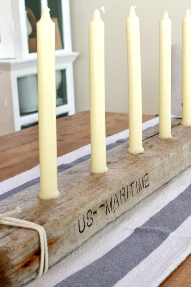 Row of candles with driftwood and stenciled words