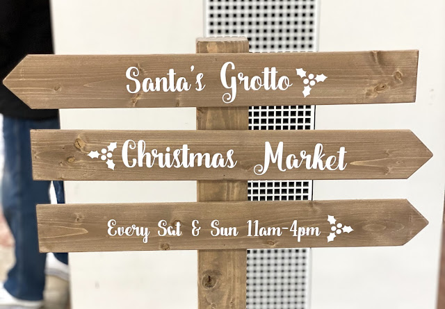 "A sign post saying ""Santa's Grotto"" one way and ""Christmas Market"" the other"