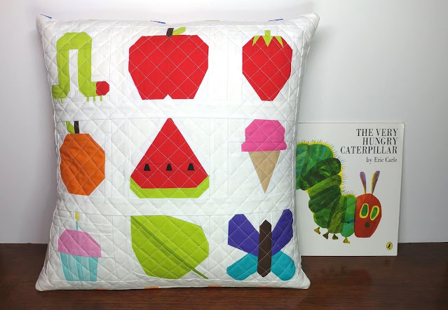 The Very Hungry Caterpillar book pocket pillow made with paper pieced quilt blocks from the I Spy book