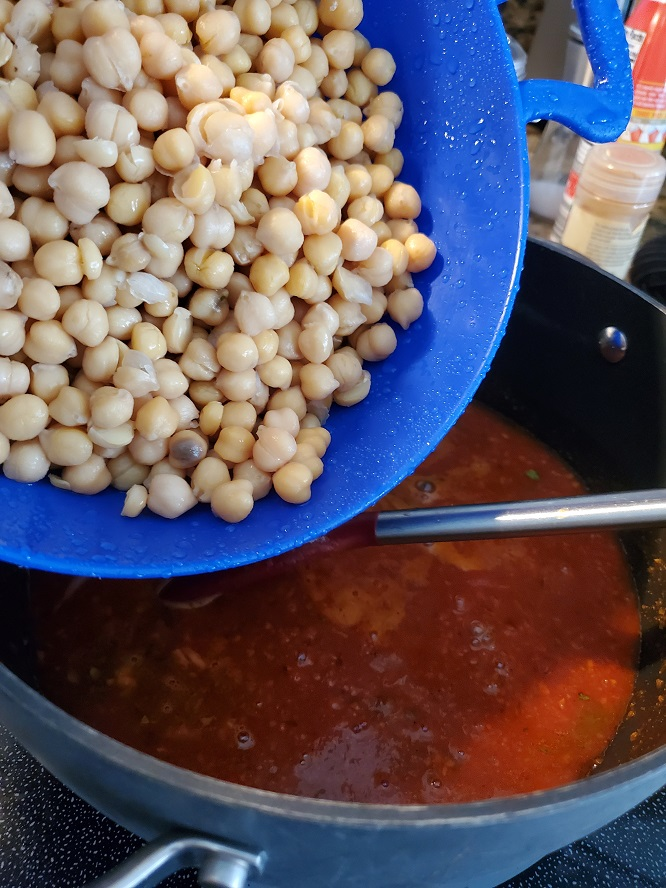 garbanzo beans in a blue colander pouring into a pot of sauce