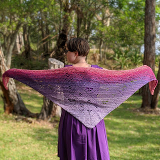 Sarah is standing with her arms out in a T holding the corners of the shawl she is wearing. It is crochet cotton yarn in a gradient from pale purple to dark purple to pink. It has filet design of a grid with motifs of flowers, butterflies and dragonflies. She is standing in a grassy clearing surrounded by trees.
