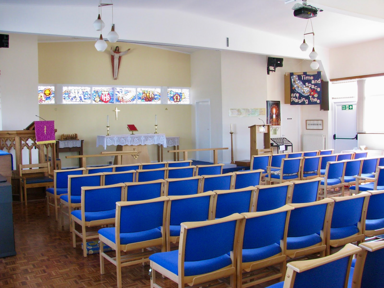 Image from Community Hall entrance to church. Parquet floor, wooden chairs with blue fabric, organ and piano to left with pulpit to left back wall, alter to centre. taken on a sunny day