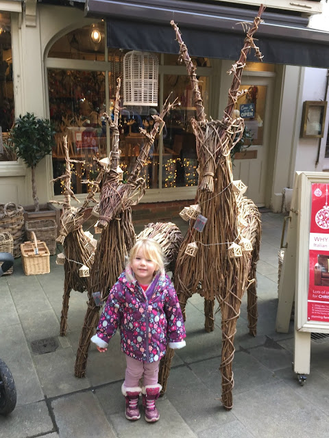 Tin Box Tot standing in front of two reindeer woven from whittle