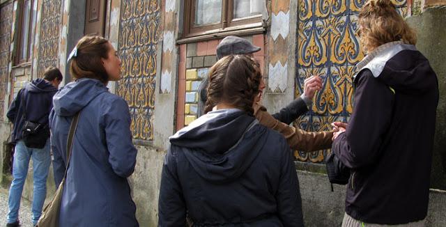 Um grupo de pessoas observando uma parede de azulejos no Porto