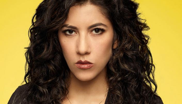 Imagem: Rosa diaz, mulher latina, de cabelos cacheados e longos. olhos castanhos e olhar sério. Usa jaqueta de couro preta.