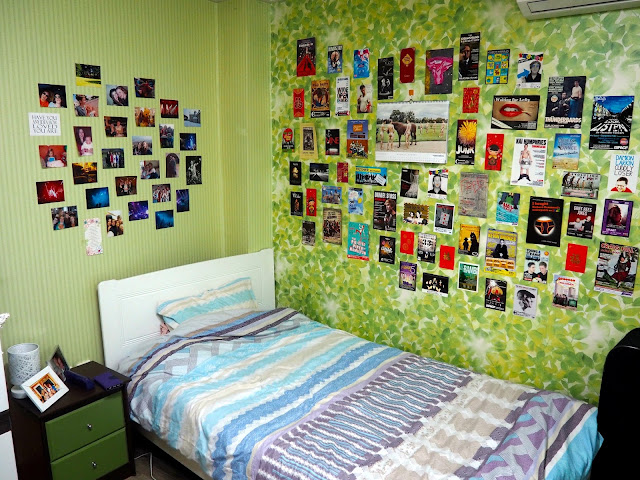 Bed area, with bedside table and pictures and photos decorating the walls, inside studio apartment in Busan, South Korea