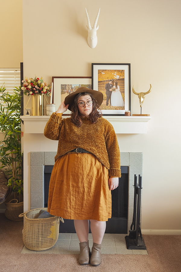 An outfit consisting of a brown panama hat, dark mustard yellow chenille sweater layered over a dark yellow linen dress and camel chelsea boots.