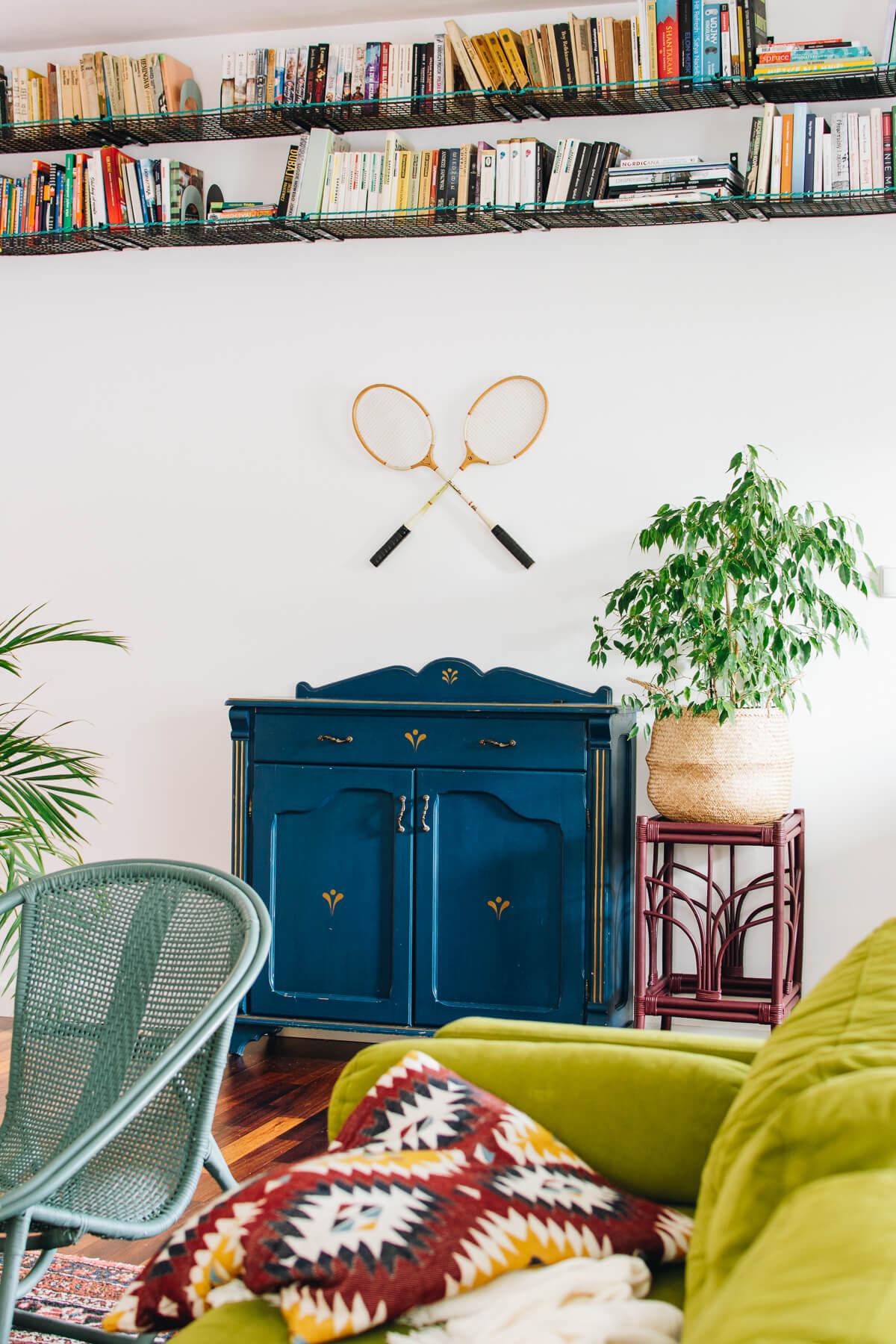 Fragment  kolorowego salonu z niebieską stylizowaną szafką, półkami na książki i zegarem w kształcie kota