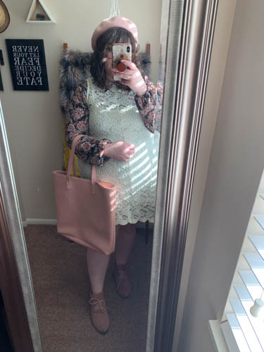 A mirror selfie of an outfit of a pink beret, black and pink and purple Peter Pan collared shift dress under white sleeveless lace dress and dusty pink desert boots.