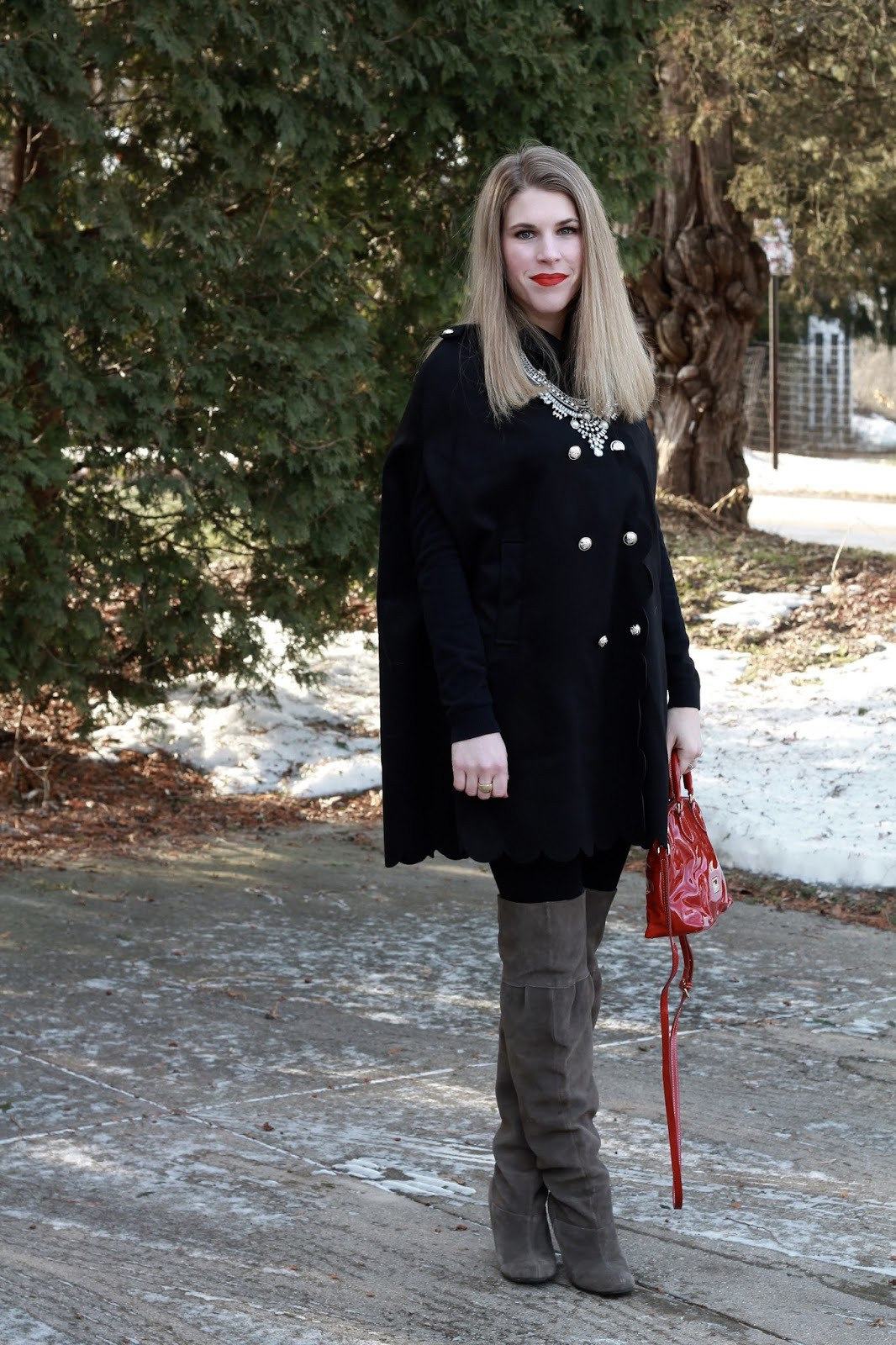 black scalloped edge cape, black leggings, taupe OTK boots, red Dooney & Bourke bag, statement necklace