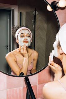 Mujer mirándose al espejo, poniéndose una mascarilla facial. Rutina de belleza.