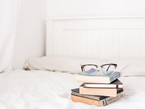 Pilha de livros em cima de uma cama num quarto clean