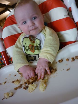Baby eating a cottage pie with their hands and making a mess