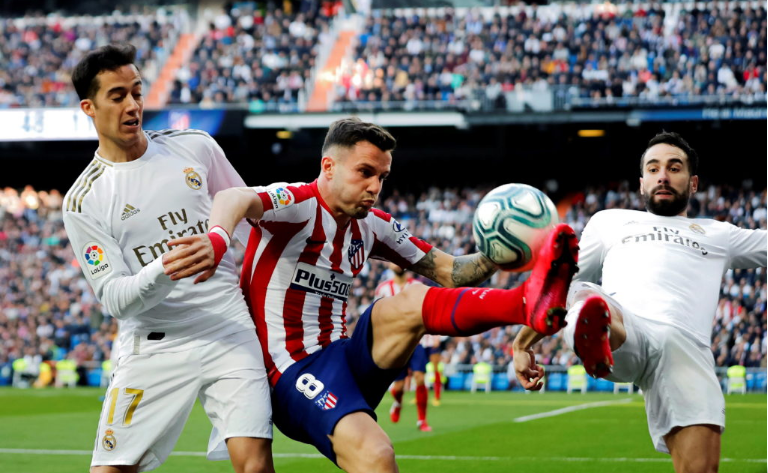 Saul Niguez challenges Real Madrid's players for control of the ball