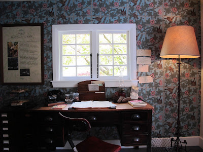 Inside view of an arts-and-crafts-style cottage, with a desk and chair under a window.