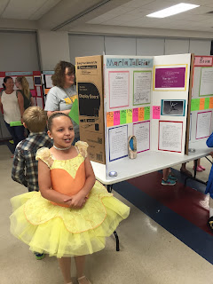 Young girl in a yellow dress standing next to her project