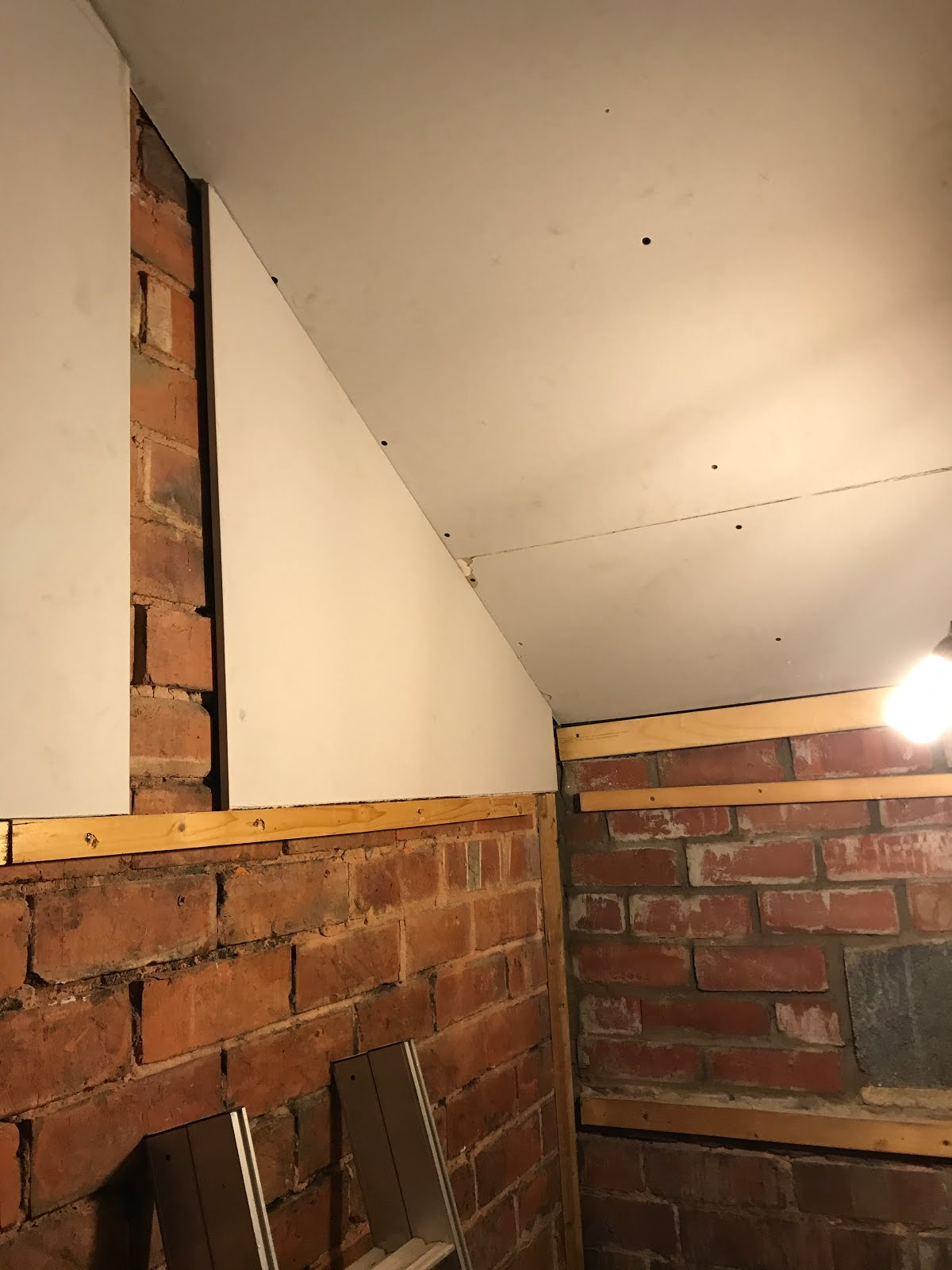 affixing plasterboard to top part of the wall