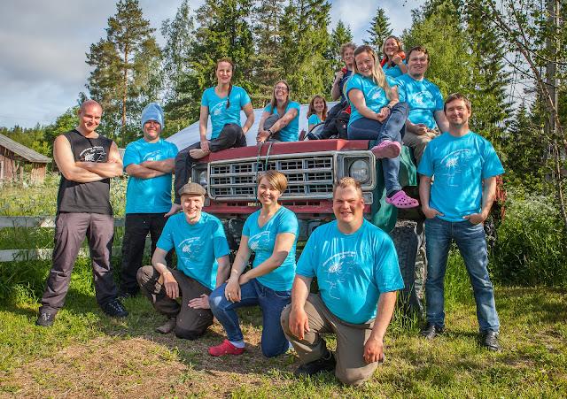 13 henkeä poseeraa vanhan autonromun ympärillä tiimipaidat päällä