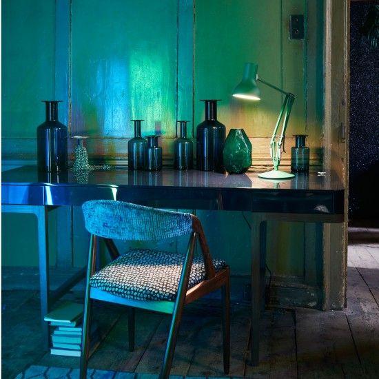 mesa de trabajao azul profundo con botellas de cristal de colores y flexo industrial chicanddeco