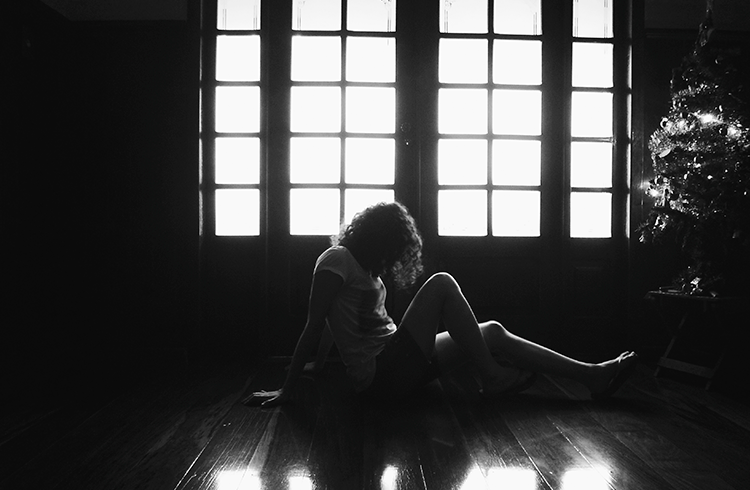A foto mostra uma sala escura, com uma porta iluminada ao fundo. À frente da porta está a autora do blog sentada, de lado, olhando para o chão. Suas mãos e pés se apoiam no assoalho da casa. Seu corpo forma uma silhueta em frente a porta iluminada