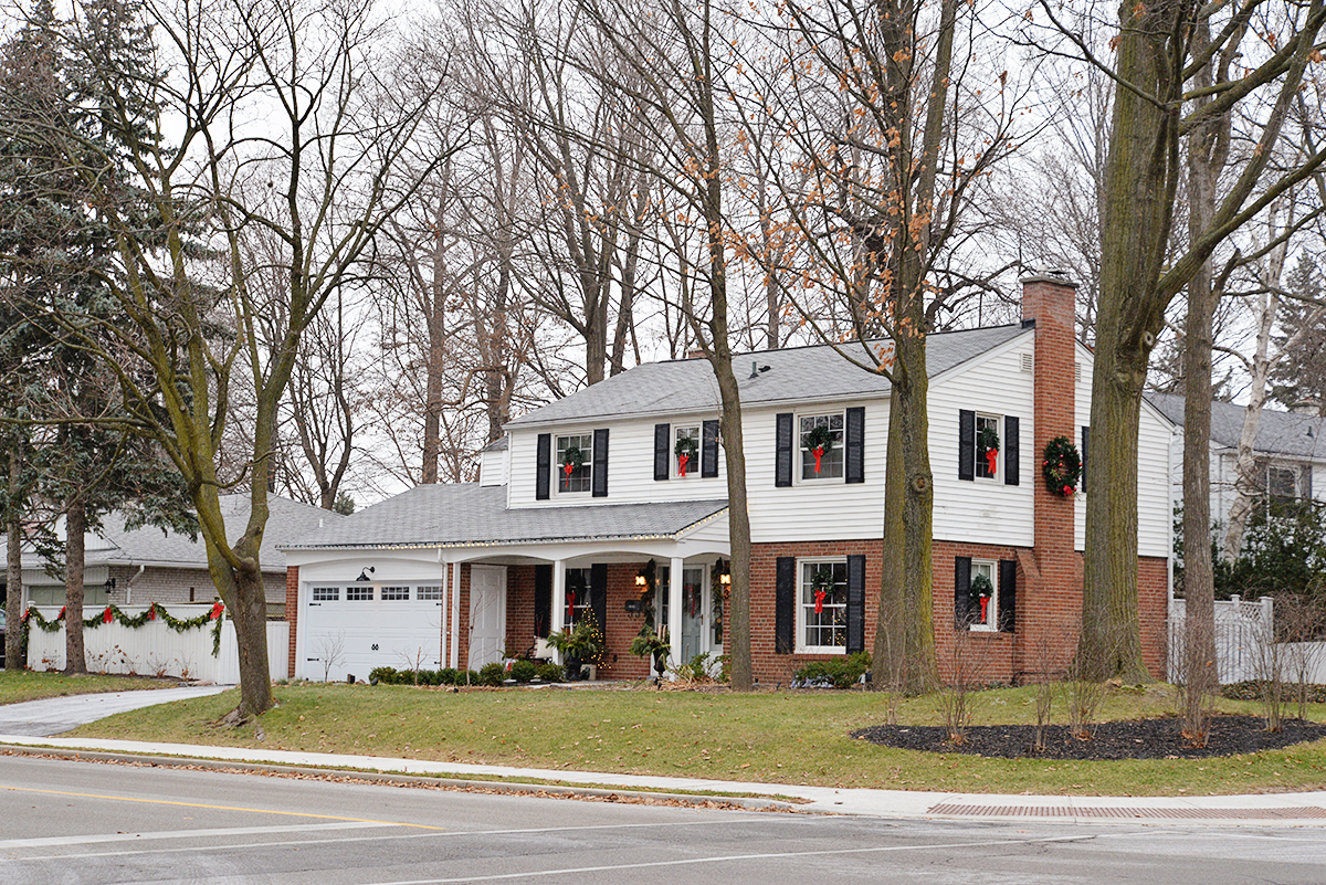 Christmas colonial house with wreaths with candles in windows. Large wreath on chimney.