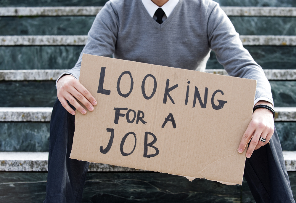 Photo showing a young man holding a cardboard sign saying 'Looking for a Job'