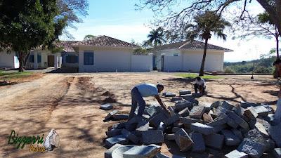 Bizzarri escolhendo as pedras folhetas de granito na cor azul claro sendo essa pedra cortada a mão para fazer as guias de pedra na rua de pedra com o piso de pedrisco.