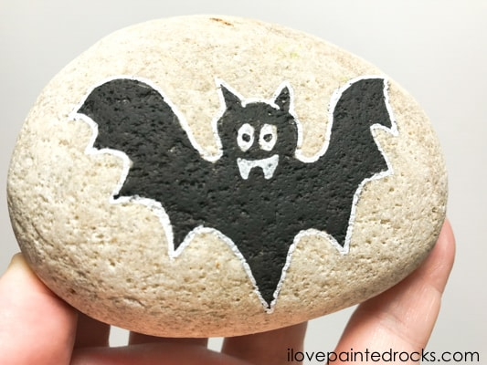 Drawing around the halloween  bat rock stone with a white posca pen