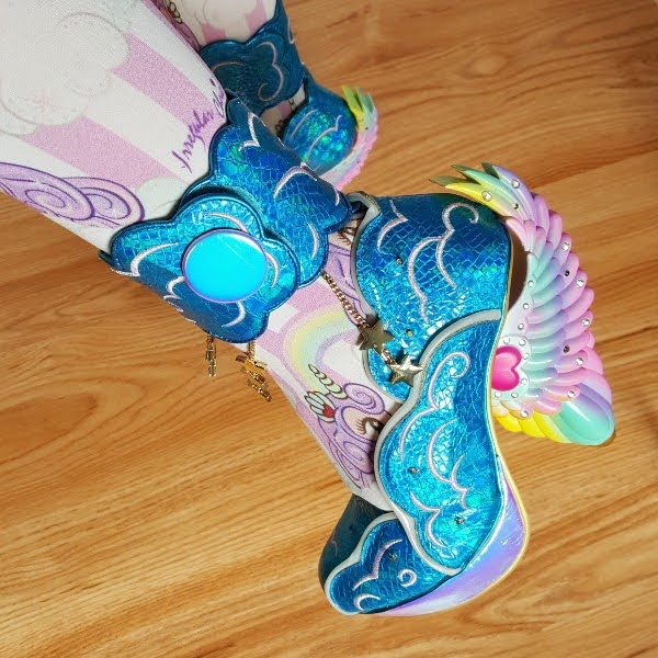 close up of rainbow wing heeled shoe on foot with striped patterned tights