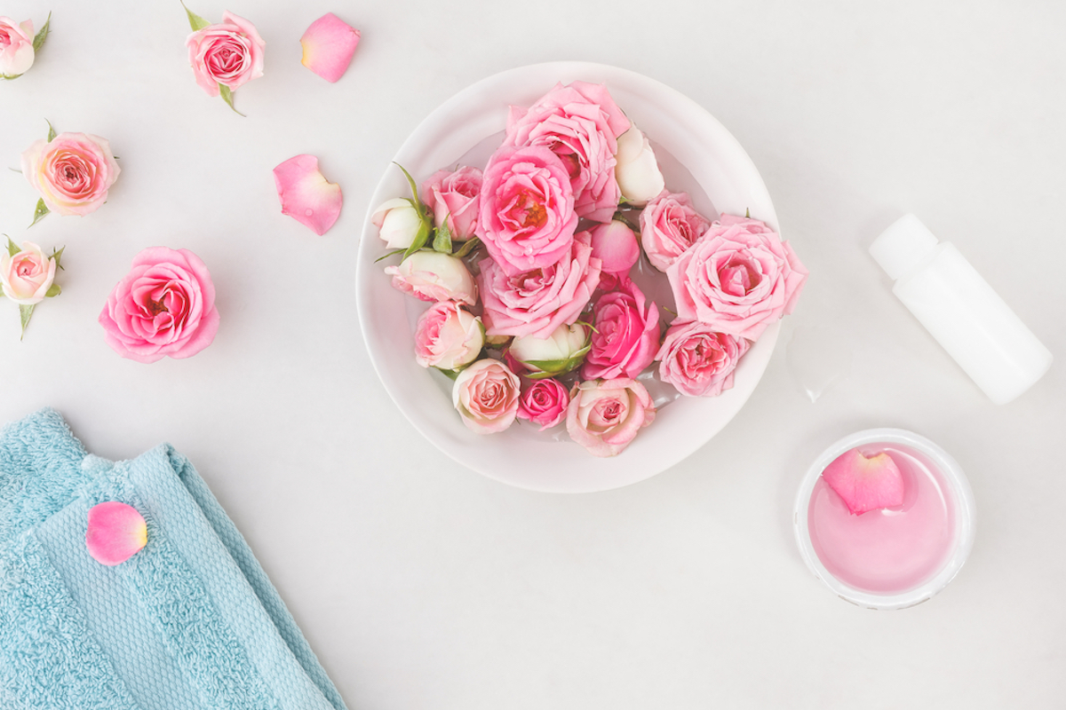This is a scene of pink roses spread out in a bathroom to create the perfect spa setting.