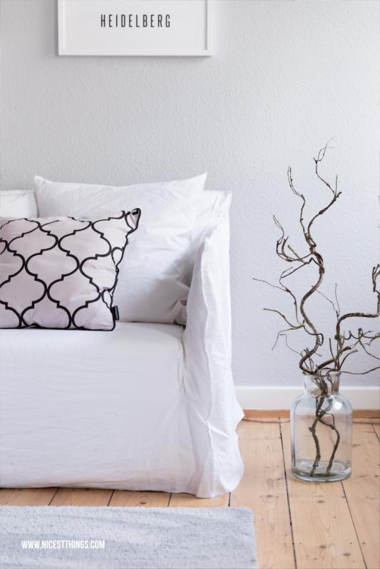 Winter Deko Wohnzimmer mit Gervasoni Ghost Sofa und Zweigen in grosser Glasvase