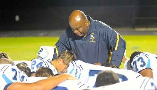 Entrenador orando con jugadores en escuela