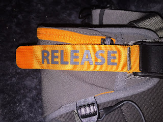 "Bright orange fabric strip with grey letters ""RELEASE"""