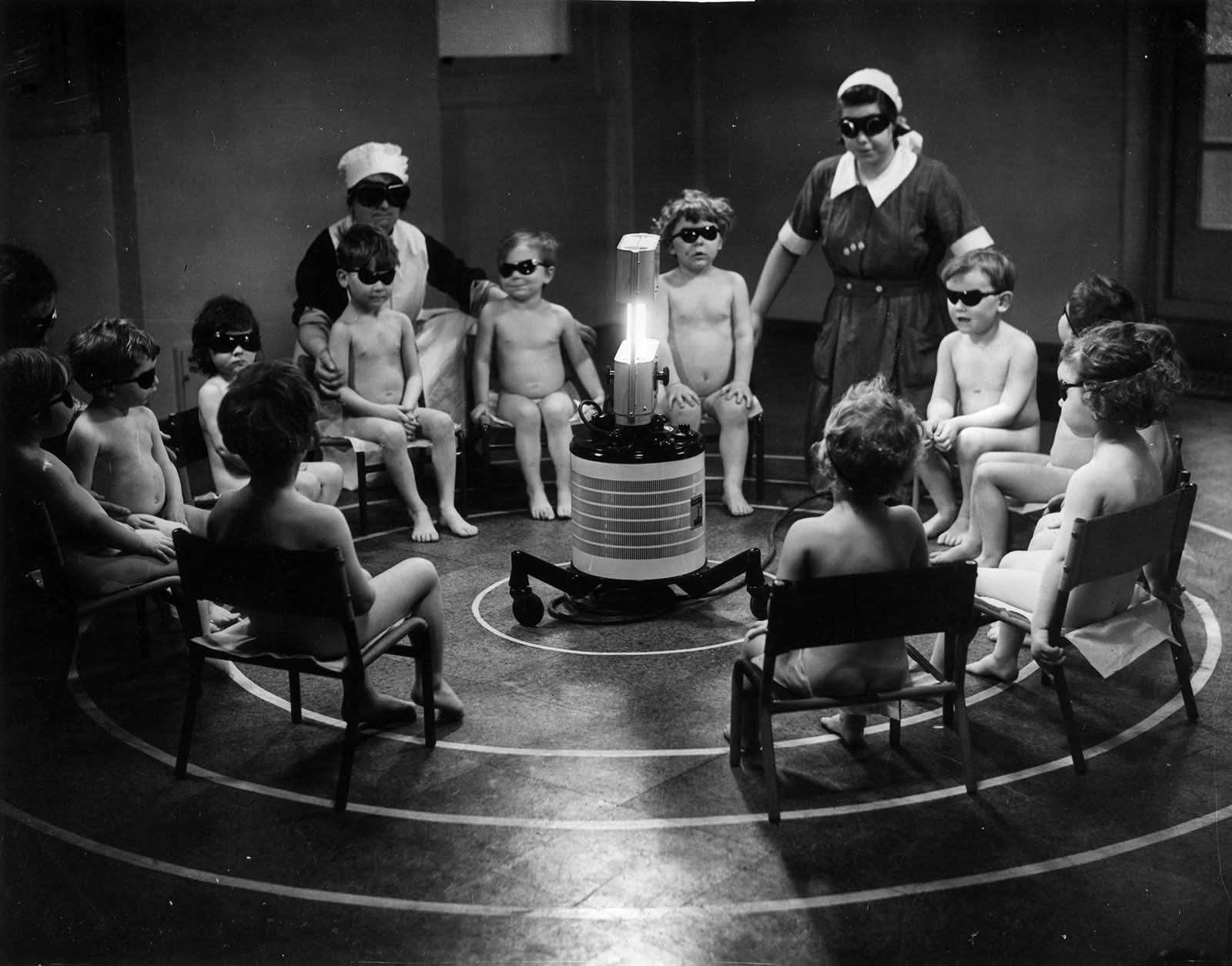 Three nurses and a group of young children sitting around a Centrosol sunray lamp at the Miriam Price Coleman day nursery. 1938.