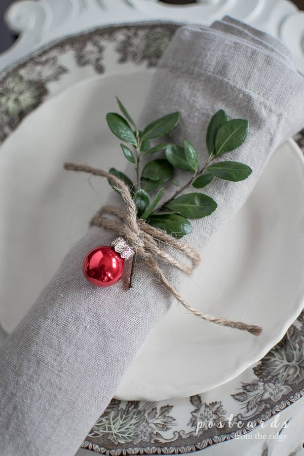 napkin ring made with twine, holly, and a tiny red Christmas ornament