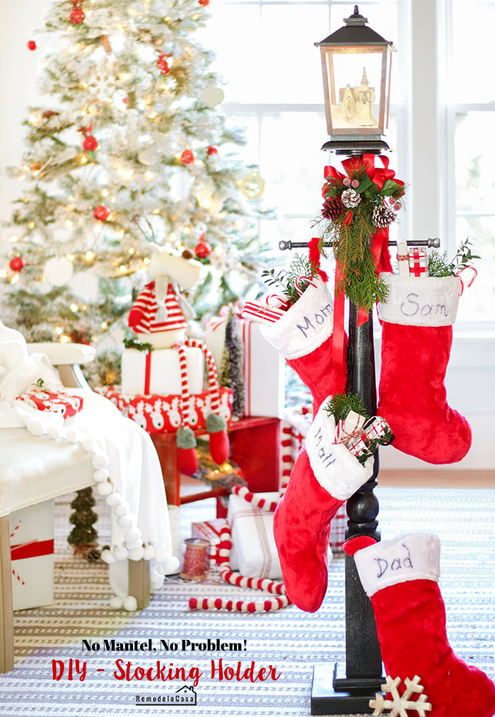 living room decorated for Christmas with red and white decor christmas tree, white chair and stocking holder  and gifts