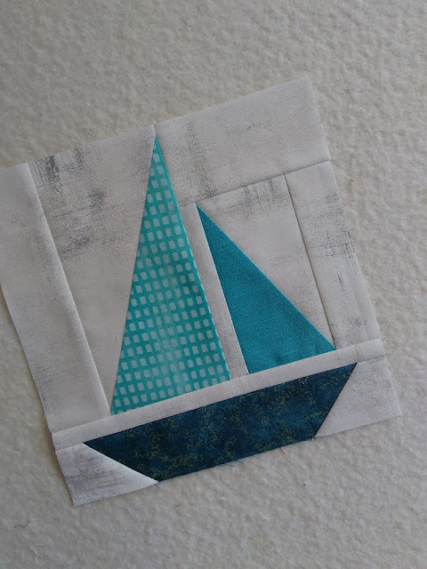Patchwork quilt block of a sailboat in teal colours