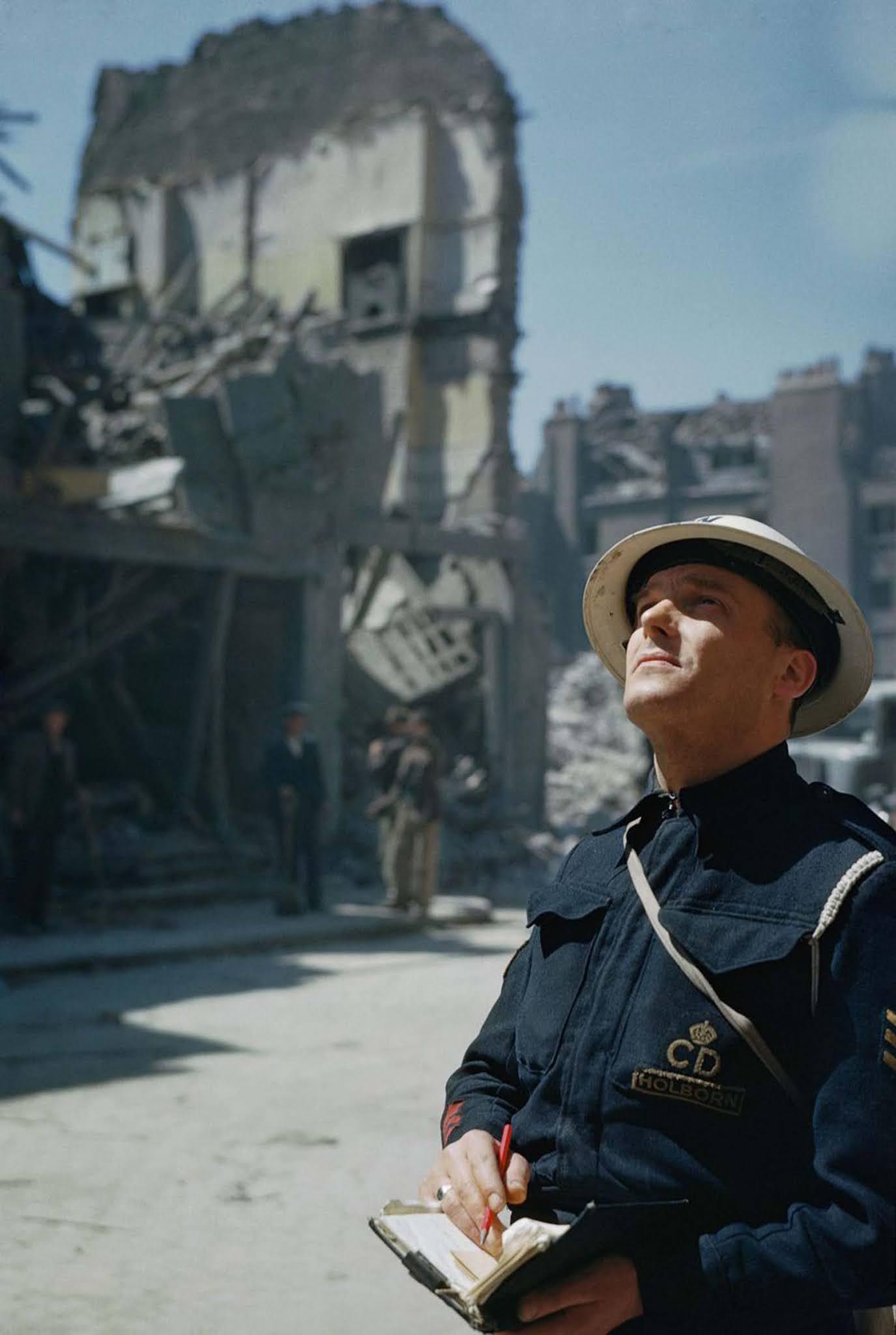 An Air Raid Precautions (ARP) warden inspects damaged buildings in Holborn, London. 1941.