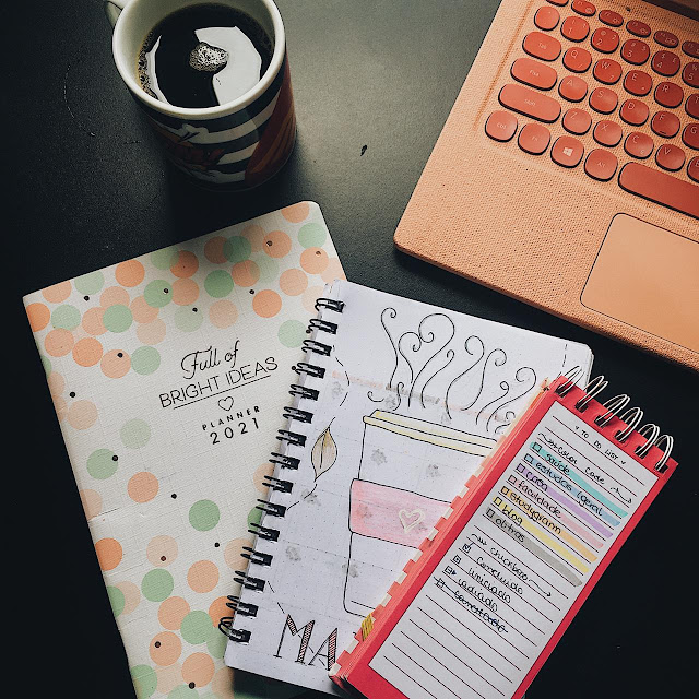 foto com um planner anual, o bullet journal aberto na capa de maio e uma caderneta de to do list