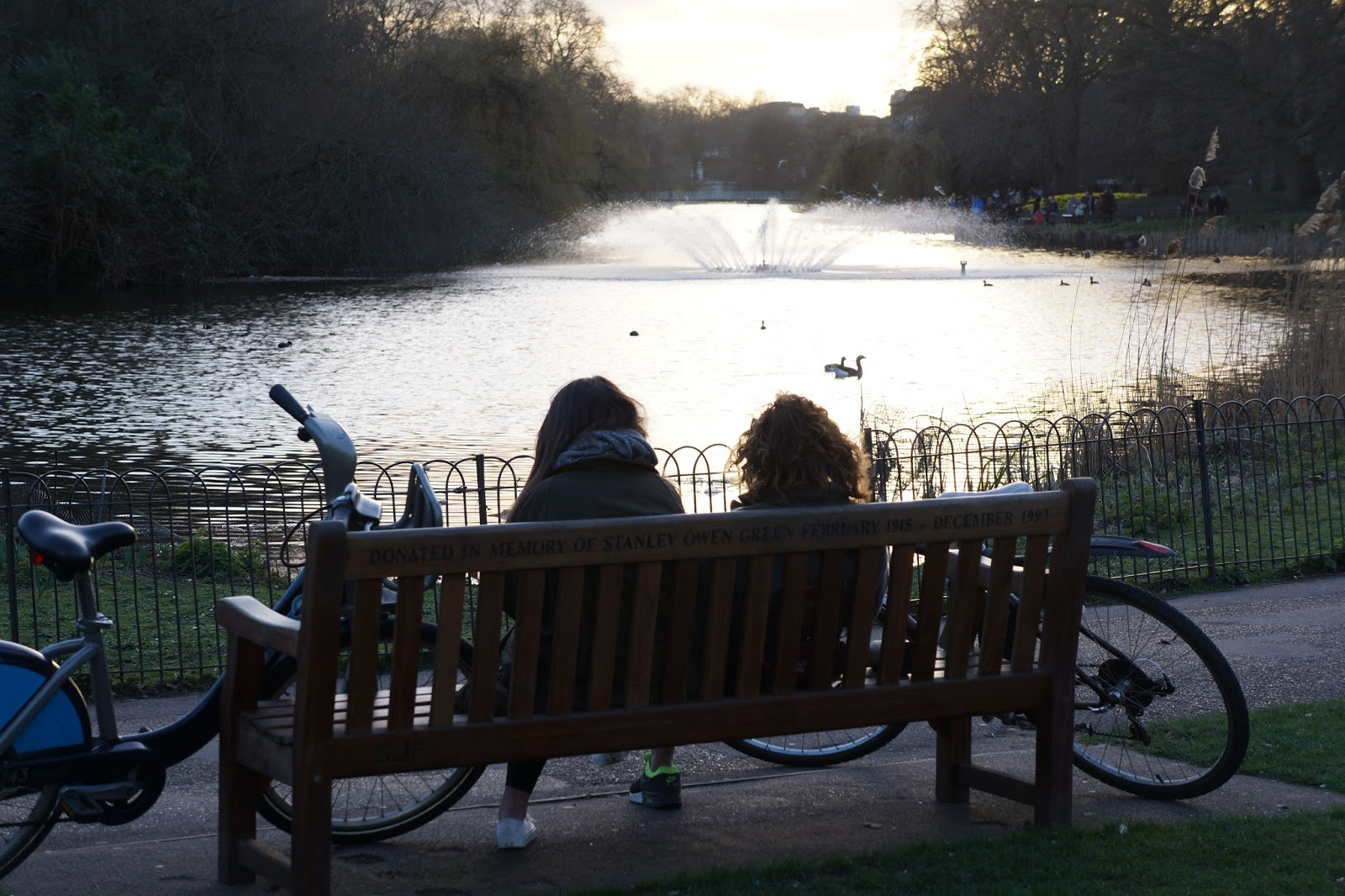 two girls sitting on a bench in front of st james's park lake