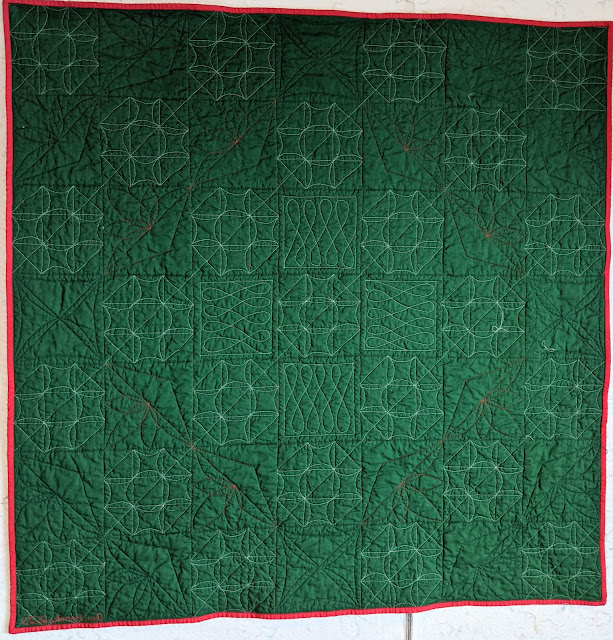 The forest green back of the quilt highlights all the quilting designs.
