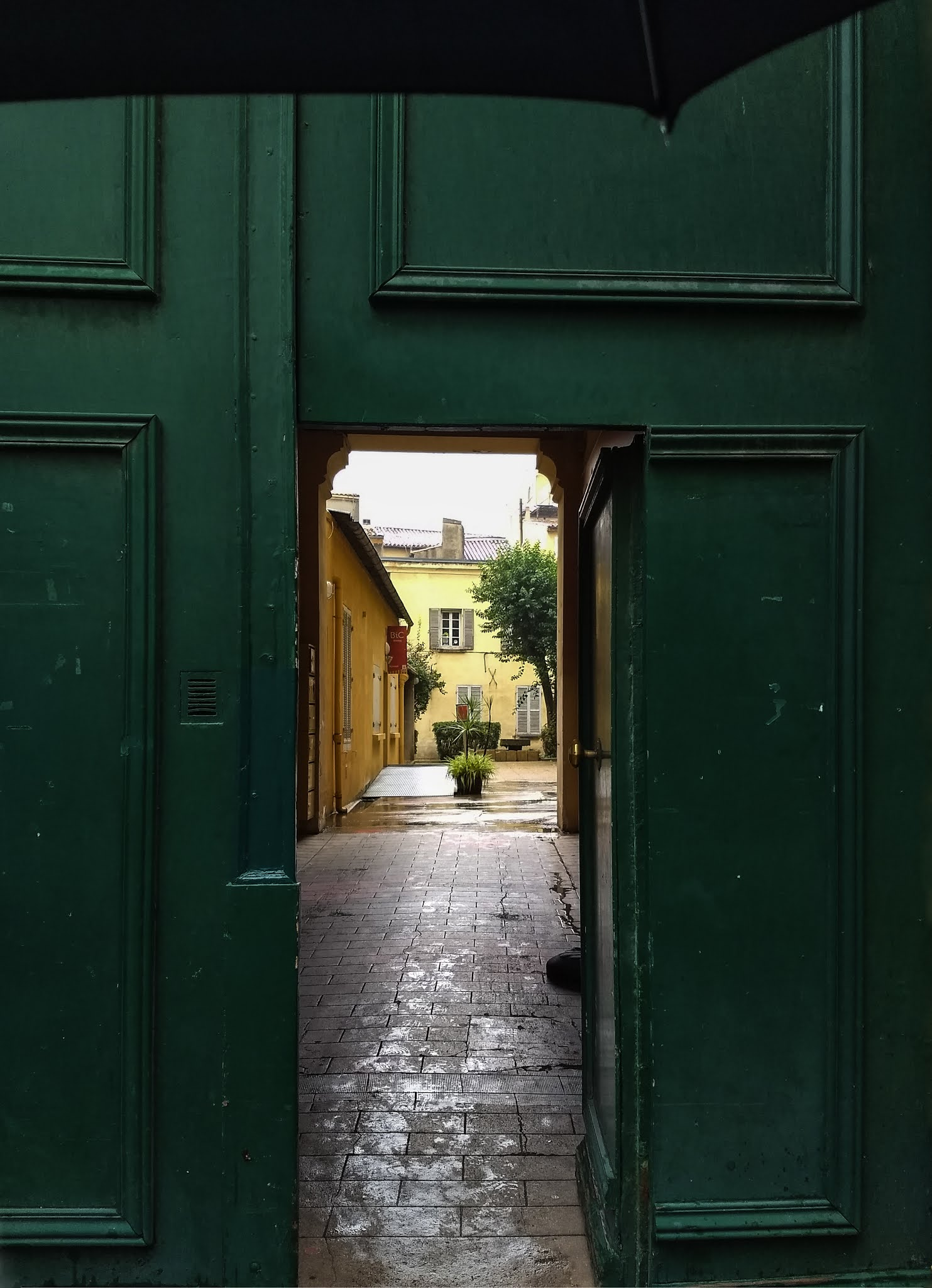 An entryway in a green doorway looking into a courtyard in Aix-en-Provence, Southern France.
